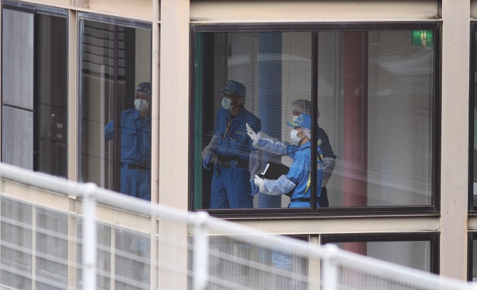 Police investigators work at the Tsukui Yamayuri-en, a facility for the disabled where 19 people were killed and dozens injured in a knife attack