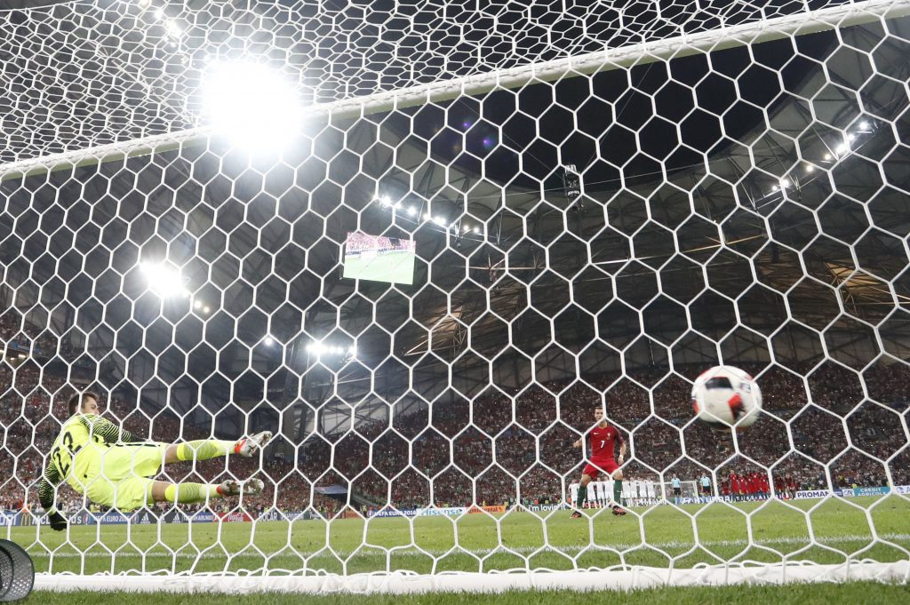 Portugal's Cristiano Ronaldo scores from the penalty spot during the penalty shootout of  the Euro 2016 quarterfinal soccer match between Poland and Portugal, at the Velodrome stadium in Marseille, France, Thursday [Friday, Macau time] (AP Photo/Martin Meissner)