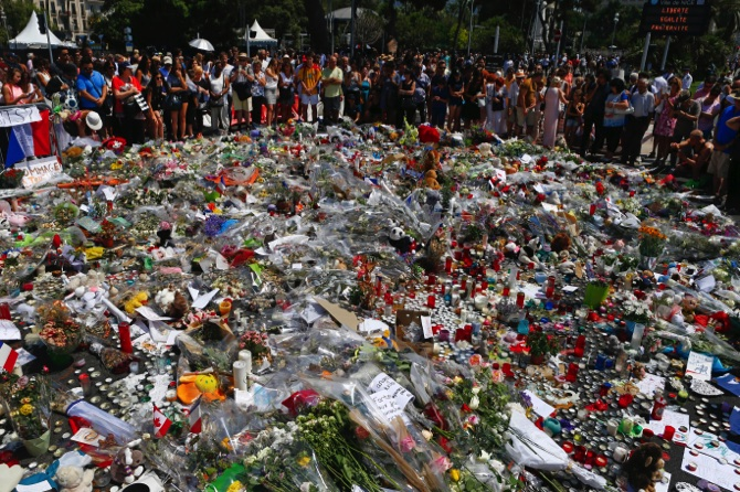 People gather at the makeshift memorial after a minute of silence on the famed Promenade des Anglais in Nice