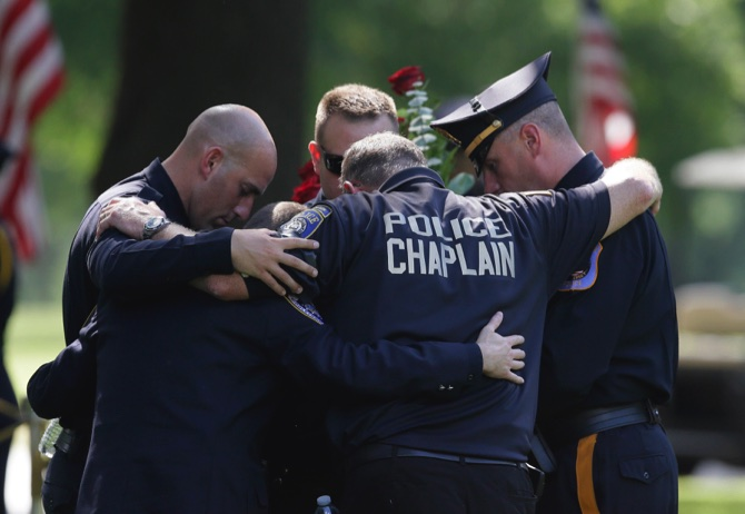 Law enforcement officers pray after the graveside service for Dallas police Sgt. Michael J. Smith