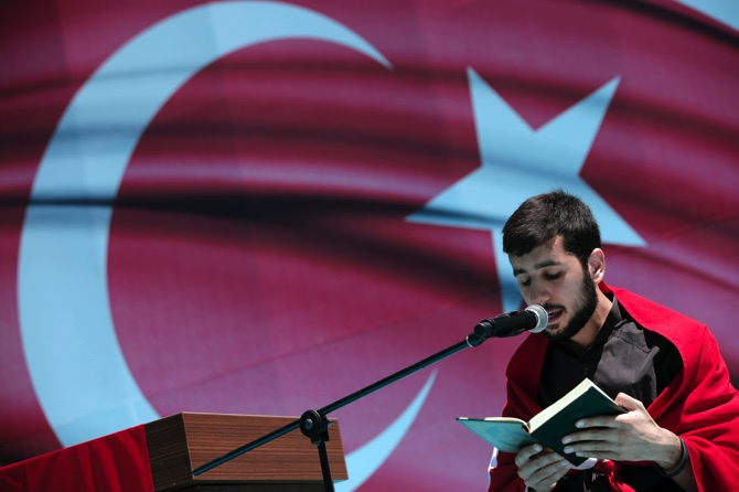 A man recites from the Quran, Islam's Holy Book, during a pro-government protest against the attempted coup
