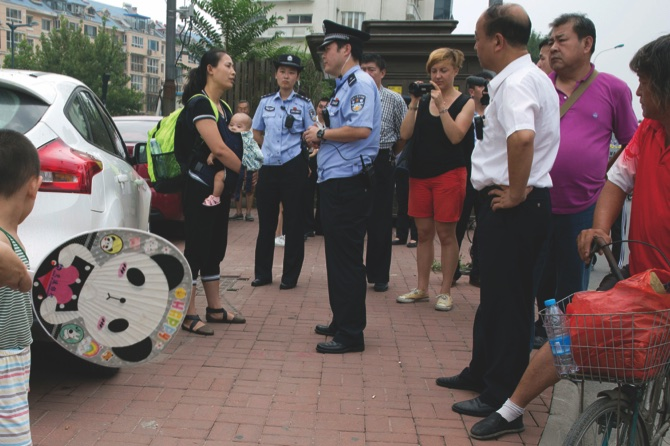 Yuan Shanshan (left) the wife of detained Chinese lawyer Xie Yanyi, is questioned by a police officer near the Tianjin No. 2 Intermediate People's Court