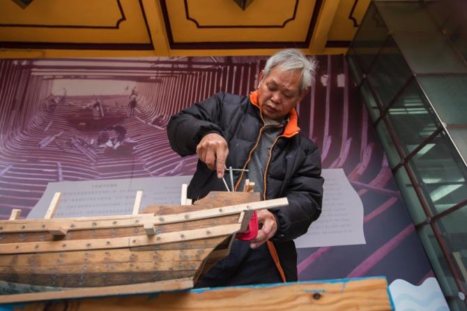 Wan Chun works on a boat model