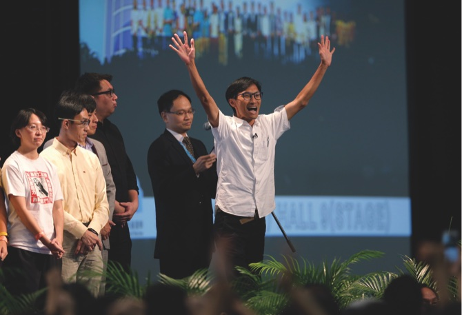 Radical activist candidate Eddie Chu Hoi-dick (right), celebrates after winning a seat at the legislative council elections in Hong Kong, yesterday