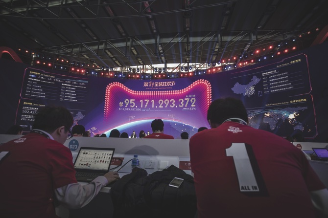 Employees work on computers while a monitor displays live updates of sales figures during the Singles' Day online shopping event in Shenzhen