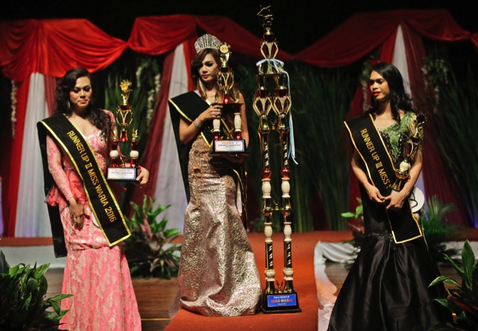 Qienabh Tappii (center), holds her trophy as she stands on the stage with first runner up Sefty Castanyo (left), and third place winner Amanda Sandova (right), after winning the Miss Transgender Indonesia pageant in Jakarta