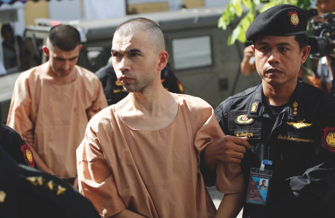 Police officers escort suspects in the Aug. 17 blast at Erawan Shrine, Bilal Mohammad (front), and Mieraili Yusufu (rear), as they arrive at a military court in Bangkok